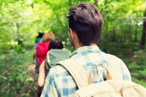 adventure, travel, tourism, hike and people concept - close up of friends walking with backpacks in woods from back